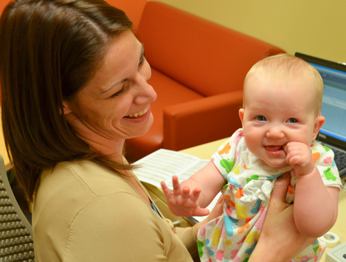a smiling audiologist holding a smiling baby