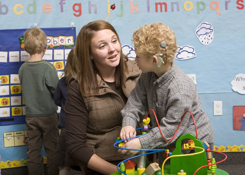 A teacher speaking with a boy who is wearing a cochlear implant in a preschool setting